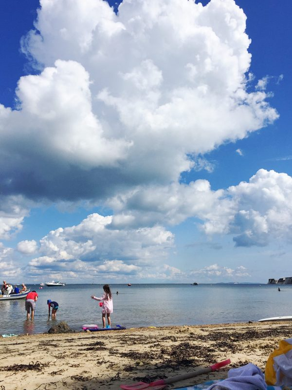 Children play on the beach under a blue sky